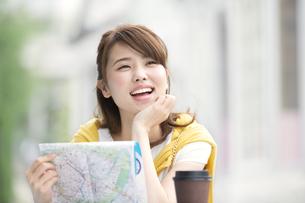 街中で地図を手に持ち微笑む女性の写真素材 [FYI02968354]