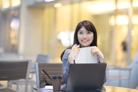 街中で手帳を持ち上を見上げ微笑むビジネス女性の写真素材 [FYI02968356]