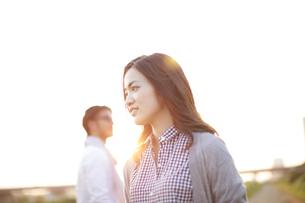 土手で遠くを眺める男性と女性の写真素材 [FYI02968358]