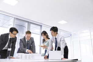 会議室で建築模型を使って打ち合せをするビジネス男女の写真素材 [FYI02968359]