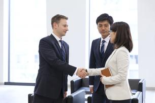 オフィスビルのロビーで握手をするビジネス男女の写真素材 [FYI02968360]