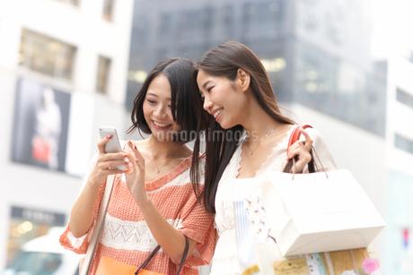 買い物中にスマートホンを見て笑う女性二人の写真素材 [FYI02968370]