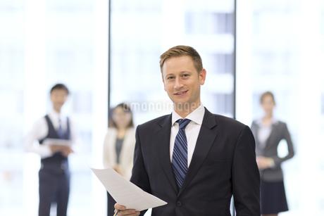 オフィスビルのロビーで資料を持って微笑むビジネス男性の写真素材 [FYI02968371]