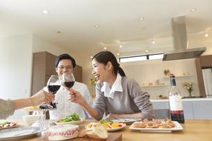 ホームパーティでワインを手に乾杯する男女三人の写真素材 [FYI02968374]