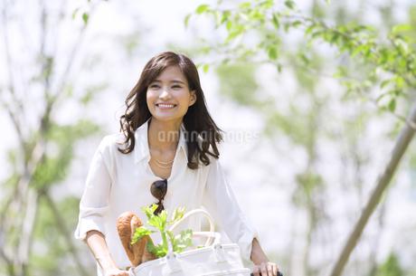 自転車で買い物をする女性の写真素材 [FYI02968378]