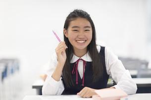 教室でペンを持って微笑む女子学生の写真素材 [FYI02968382]