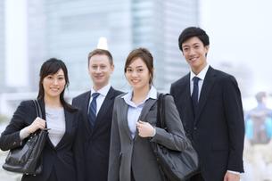 オフィスビルを背景に微笑むビジネス男女の写真素材 [FYI02968387]