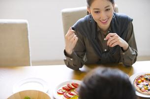 ダイニングテーブルで食事を楽しむ男性と女性の写真素材 [FYI02968388]
