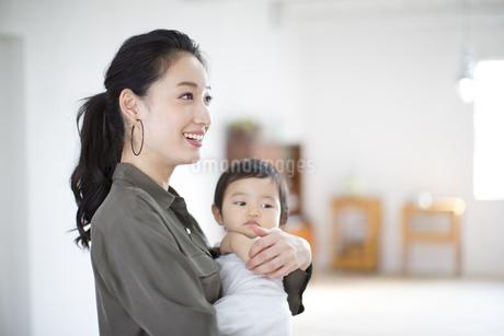 赤ちゃんを抱き抱えて微笑む女性の写真素材 [FYI02968389]