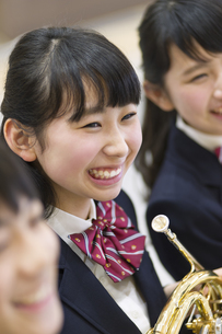 ホルンを持って微笑む女子学生の写真素材 [FYI02968391]