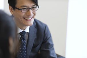 オフィスビルのロビーで笑うビジネス男性の写真素材 [FYI02968395]