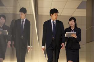 歩きながら打ち合せをするビジネス男女の写真素材 [FYI02968397]