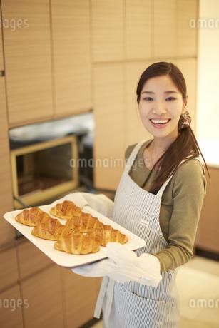 焼いたクロワッサンを持った主婦のスナップの写真素材 [FYI02968401]