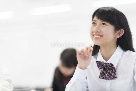 教室でペンを持ち考える女子学生の写真素材 [FYI02968403]