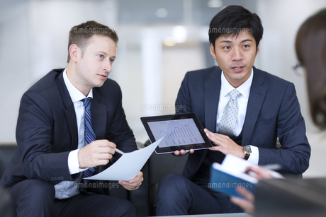 タブレットPCを持ち打ち合せをするビジネス男性の写真素材 [FYI02968404]