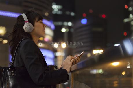 夜の街を背景にヘッドフォンを付けてリラックスするビジネス女性の写真素材 [FYI02968406]