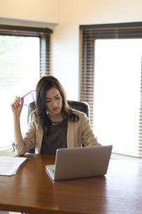 オフィスのデスクでパソコンを見るビジネス女性の写真素材 [FYI02968409]