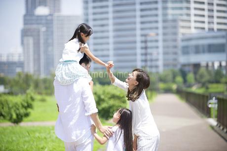 肩車して遊歩道を歩く家族の後ろ姿の写真素材 [FYI02968412]