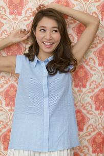 壁に寄り掛かって笑う女性の写真素材 [FYI02968414]