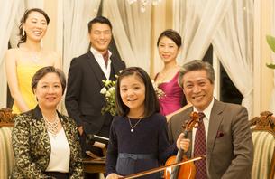 バイオリンを持った女の子と笑顔の家族の写真素材 [FYI02968427]