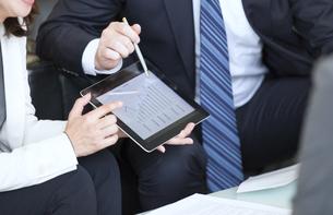 タブレットPCを持ち打ち合せをするビジネス男女の手元の写真素材 [FYI02968429]