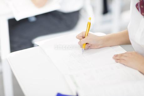 ノートに文字を書く女子学生の手元の写真素材 [FYI02968434]