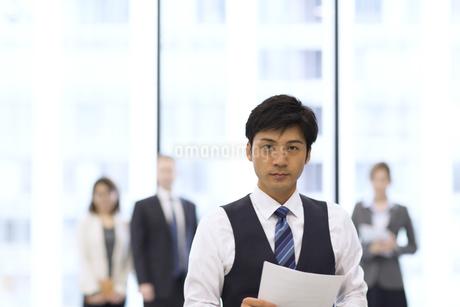 オフィスビルのロビーで資料を持って立つビジネス男性の写真素材 [FYI02968435]