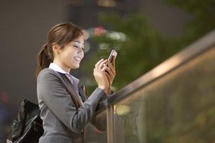 夜の街を背景にスマートフォンを見て笑うビジネス女性の写真素材 [FYI02968437]