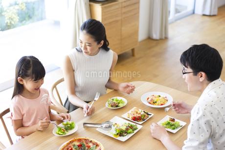 ダイニングテーブルで食事を楽しむ家族の写真素材 [FYI02968442]
