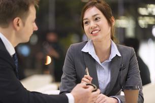 オフィスビルのロビーで打ち合せをするビジネス男女の写真素材 [FYI02968444]