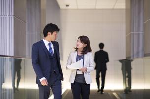 歩きながら打ち合せをするビジネス男女の写真素材 [FYI02968446]