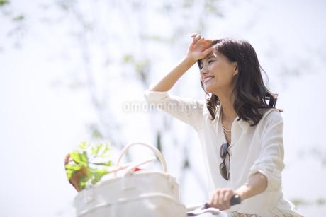 自転車で買い物をする女性の写真素材 [FYI02968448]