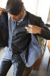オフィスでスーツのジャケットを羽織るビジネス男性の写真素材 [FYI02968449]