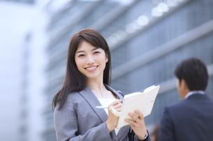 ビルを背景に立つビジネス女性の写真素材 [FYI02968452]