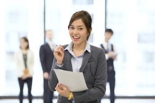 オフィスビルのロビーで資料を持って微笑むビジネス女性の写真素材 [FYI02968453]