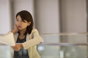 資料を持ち上を見上げるビジネス女性の写真素材 [FYI02968455]