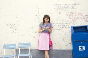 壁に寄り掛かってスマートフォンを操作する女性の写真素材 [FYI02968456]
