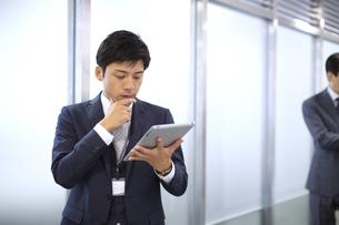 オフィスの廊下でタブレットPCを操作するビジネス男性の写真素材 [FYI02968462]