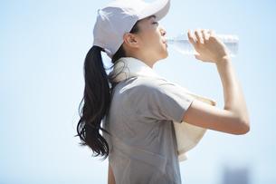 運動後にミネラルウォーターを飲む女性の横顔の写真素材 [FYI02968463]