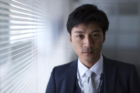 オフィスの窓際で立つビジネス男性の写真素材 [FYI02968468]