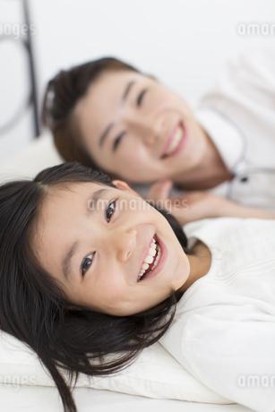 横になって笑う母と娘の写真素材 [FYI02968470]