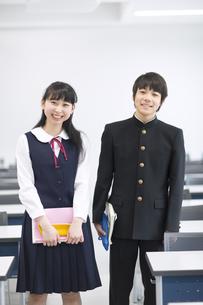 教室で教材を持って笑う男子学生と女子学生の写真素材 [FYI02968471]