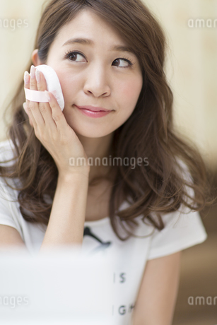 鏡の前でスキンケアをする微笑む女性の写真素材 [FYI02968473]