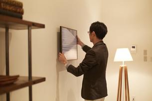 壁に写真を飾る男性の写真素材 [FYI02968487]