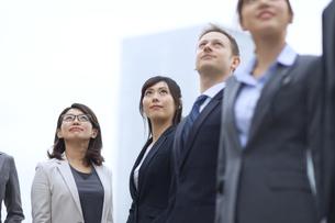 オフィスビルを背景に上を見上げて立つビジネス男女の写真素材 [FYI02968490]