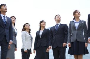 オフィスビルを背景に上を見上げて立つビジネス男女の写真素材 [FYI02968493]