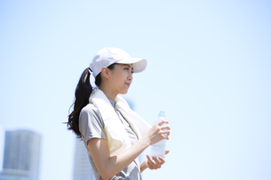 ミネラルウォーターを持って遠くを眺める女性の写真素材 [FYI02968496]