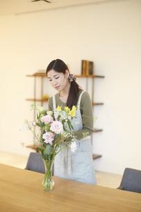 窓際で花瓶の花を見る主婦の写真素材 [FYI02968503]