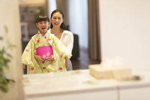 鏡の前で子供に浴衣を着せる母親の写真素材 [FYI02968510]