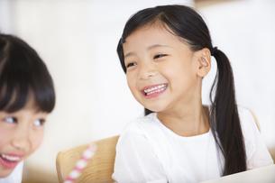 椅子に座って笑う女の子の写真素材 [FYI02968514]